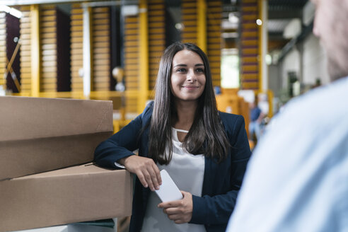Young woman working in distribution warehouse, talking to colleague - KNSF04962