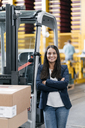 Confident woman standing in logistics center, with arms crossed - KNSF04965