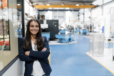 Confident woman working in high tech enterprise, standing in factory workshop with arms crossed - KNSF04968