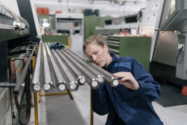 Young woman working as a skilled worker in a high tech company, checking steel rods - KNSF04980