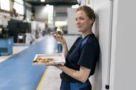 Woman working in high tech company, taking a break, eating pizza - KNSF04989