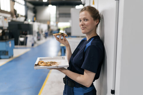 Woman working in high tech company, taking a break, eating pizza - KNSF04989