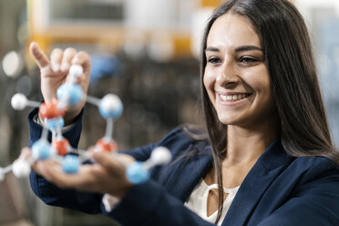 Confident woman working in high tech enterprise, holding molecule model - KNSF04992