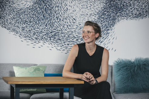 Woman sitting in modern office space, smiling - MFF04710