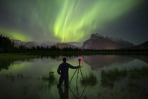 Aurora Borealis over photographer with tripod in lake and mountains in Banff National Park, Alberta, Canada - AURF06534