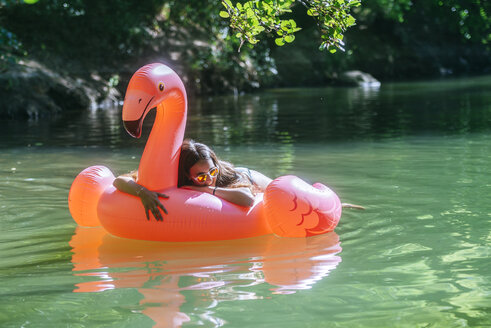 Woman floating on water on an inflatable flamingo - KIJF02026