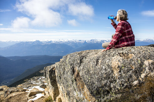 Female hiker resting and drinking water at top of Whistler Mountain, Garibaldi Provincial Park, Whistler British Columbia, Canada - AURF06821