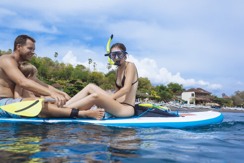Family on sup surfboard in ocean,Bali,Indonesia - AURF06890