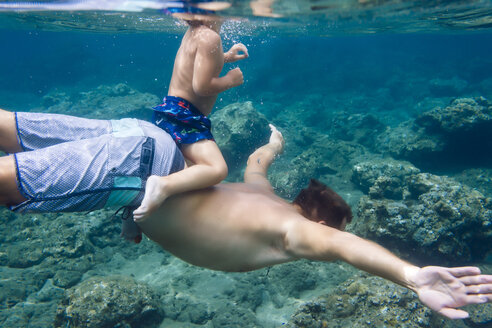 Father and son diving under water,Bali,Indonesia - AURF06896