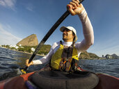 Man kayaking in Baia de Guanabara with Pao de Acucar mountain in background, Rio de Janeiro, Brazil - AURF07064