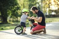 Father supporting little son on bike - HAPF02741