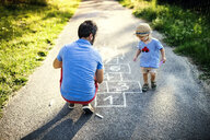 Father playing hopscotch together with his little son - HAPF02747