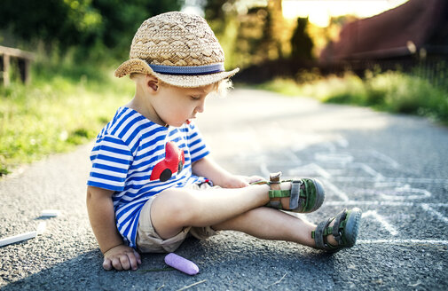 Toddler boy sitting on the street taking off his shoes - HAPF02750