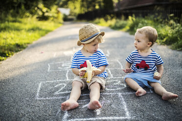 Toddler boy and his little sister sitting together on the street eating bananas - HAPF02759