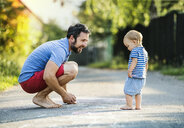 Father playing with his little daughter on the street in summer - HAPF02768