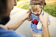 Father putting on pilot hat for his little son - HAPF02777