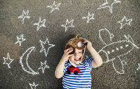 Smiling toddler with pilot hat and goggles lying on asphalt painted with airplane, moon and stars - HAPF02780