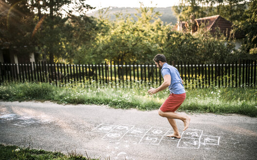 Man playing hopscotch with naked feet - HAPF02786