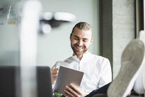 Smiling businessman sitting in office with feet up using tablet - UUF15178