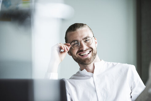 Portrait of smiling young businessman in office - UUF15181