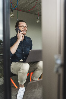 Smiling young businessman on cell phone in office - UUF15214