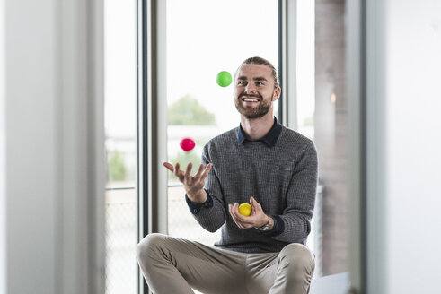 Smiling young businessman sitting at the window juggling with balls - UUF15244