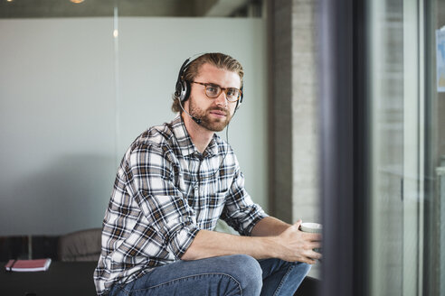 Casual businessman with cup of coffee and headset in office - UUF15253
