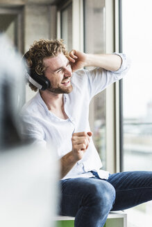 Happy casual young man listening to music with headphones at the window - UUF15262
