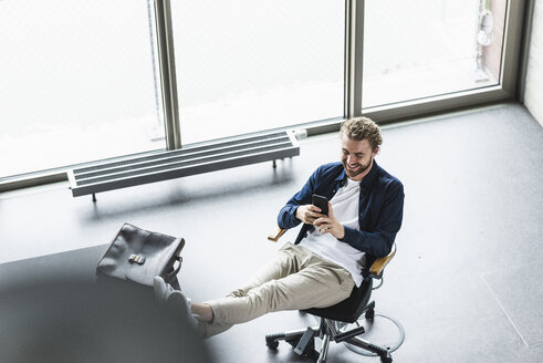 Smiling casual businessman sitting in office with feet up using cell phone - UUF15274