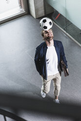 Casual young businessman playing football in office - UUF15280