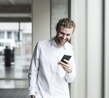 Smiling young businessman looking at cell phone at the window in office - UUF15283