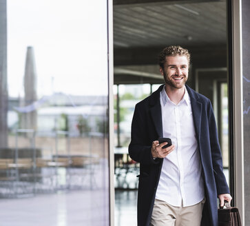 Smiling young businessman holding cell phone leaving office - UUF15286