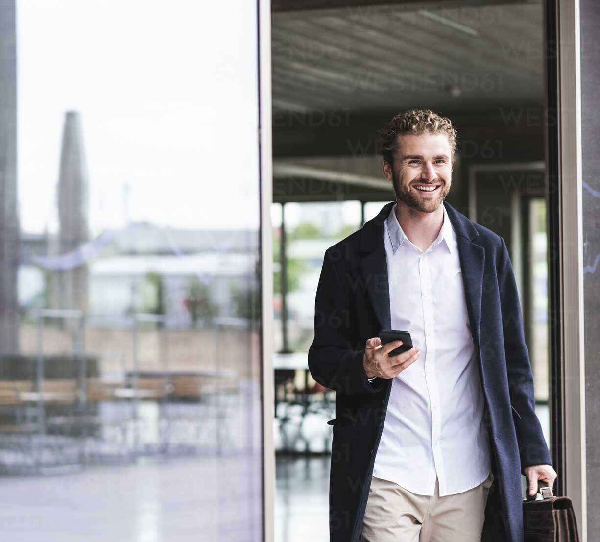 Smiling young businessman holding cell phone leaving office - UUF15286 - Uwe Umstätter/Westend61