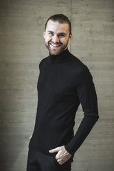 Portrait of smiling young man wearing black turtleneck jumper - UUF15292