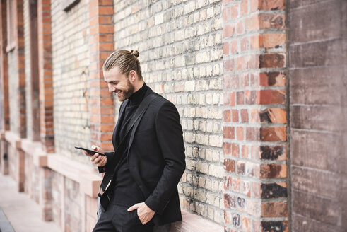 Smiling fashionable young man standing at brick wall using cell phone - UUF15295