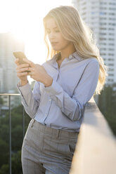 Blonde business woman checking smartphone on city rooftop - SBOF01504