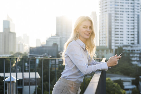 Blonde smiling business woman leaning onto handrail holding smartphone on city rooftop - SBOF01507