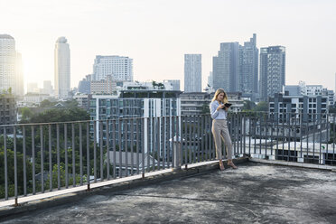 Blonde business woman leaning onto handrail holding tablet on city rooftop - SBOF01510