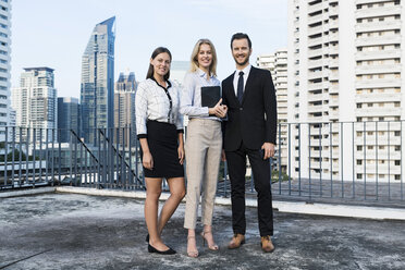 Group of successful business people on city rooftop, holding digital tablet - SBOF01516