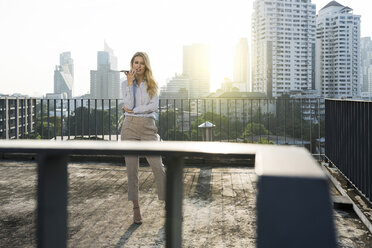 Business woman speaking into smartphone on city rooftop - SBOF01522