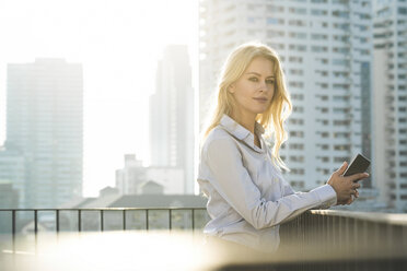 Portrait of blonde business woman leaning onto handrail on city rooftop - SBOF01525