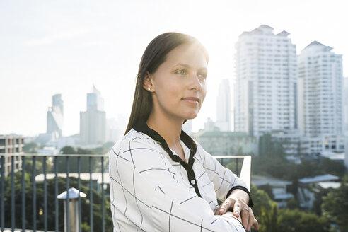 Portrait of brunette business woman on rooftop - SBOF01531