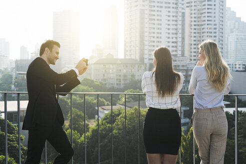 Businessman taking picture of his female colleagues on city rooftop - SBOF01534