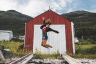 Young woman jumping in front of red barn in Nothern Norway - KKAF02031