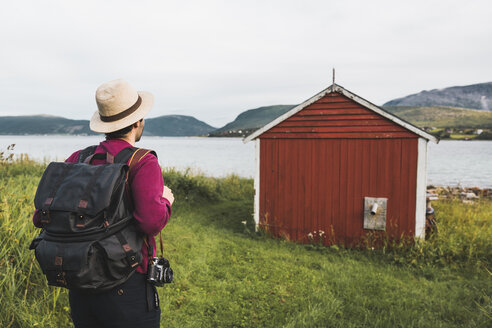 Young man with backpack exploring red barn in Northern Norway - KKAF02034