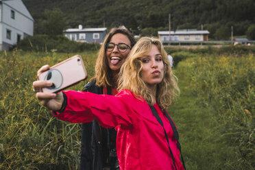 Traveling friends taking smartphone selfies in Northern Norway - KKAF02037