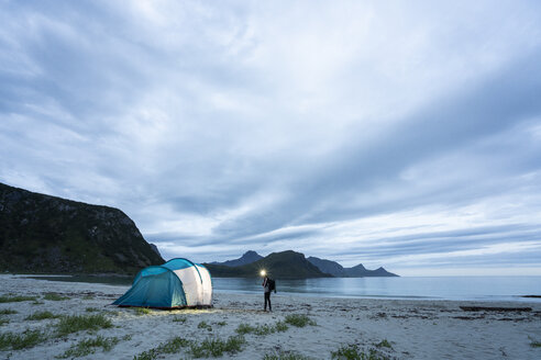 Norway, Lapland, Person standing by tent on a beach at fjord - KKAF02067