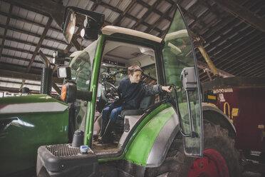 Teenage boy operating tractor on farm, Chilliwack, British Columbia, Canada - AURF07313