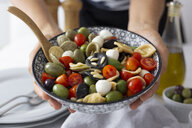 Woman showing mediterranean orecchiette with tomato, olives and mozzarella - GIOF04540