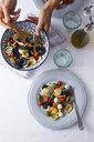 Woman serving mediterranean orecchiette with tomato, olives and mozzarella - GIOF04546